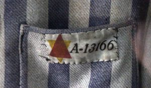 Closeup of a prisoner's identification number and symbol (signifying the reason for imprisonment) on a uniform on display in the Auschwitz I museum.