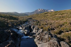 Crossing a creek with Mount Ruapehu in the background.