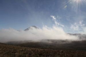 A cloud sweeping past the trail with Mount Ngauruhoe behind it.