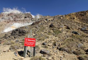 "Sign warning hikers not to stop due to danger of ""volcanic flying rock."""