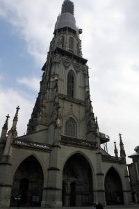 The façade of the Cathedral of Bern with its tall bell tower undergoing renovation.