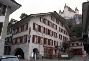 Zunfthaus zu Metzgern (a hotel and restaurant in Thun) with Thun Castle towering over from behind.