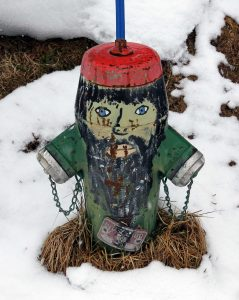 A fire hydrant painted to look like a gnome.