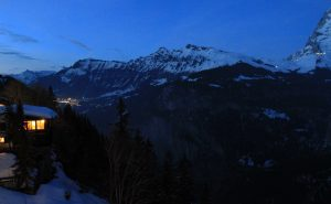 The Lauterbrunnen Valley at night with the village of Wengen's lights visible in the distance.