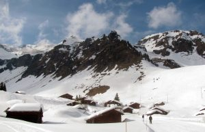 Skiers casually passing between alpine huts.