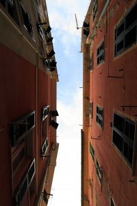 Looking up from a street at the gap between buildings in Vernazza.