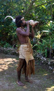Man blowing into a shell trumpet at Ekasup Cultural Village.