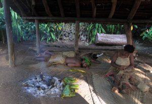 A woman weaving a basket while two men sleep.